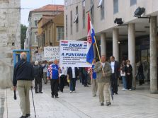 Protestors in Zadar, Croatia carry signs.