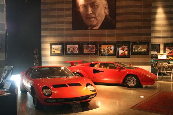 The Lamborghini Muira (on the left) and Countach (right) on display under a photo of Ferruccio Lamborghini.